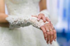 Bride wears wedding gloves Stock Photos