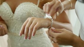 The bride wears wedding jewelry, put bracelet on wrist.  stock footage