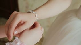 The bride wears wedding jewelry, put bracelet on wrist.  stock video footage