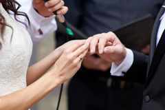 Bride wears a wedding ring on finger of groom Royalty Free Stock Images