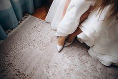 Bride wears wedding shoes. stock photos