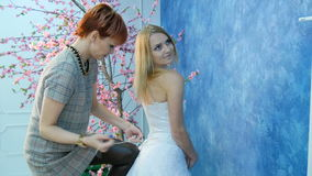 The bride wears a white dress. Girlfriend helps tie the braid stock footage