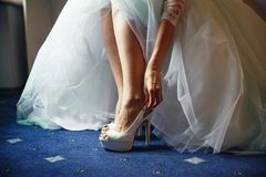 Bride puts on white shoes in preparation for the wedding royalty free stock images