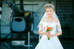 Bride with wedding bouquet on background of helicopter in hangar Royalty Free Stock Photos