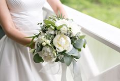 Bride with wedding bouquet. Morning at wedding day at summer. Beautiful mix white peonies and eucalyptus Stock Photography