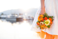 The bride with wedding bouquet from orange flowers, pomegranate, gerberas. She is dressed in white wedding dress with orange. Underskirt. Girl stands in the stock photo