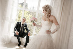 Bride with a wedding bouquet from roses and the groom sitting at a window Stock Images