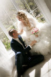 Bride with a wedding bouquet from roses and the groom sitting at a window Stock Image