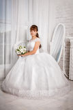 Bride with wedding bouquet sits in an armchair stock images