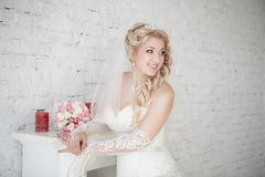 Bride with wedding bouquet standing near fireplace Royalty Free Stock Image