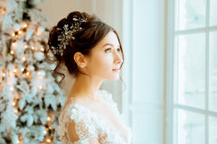 Bride. Wedding. The bride in a short dress with lace in the crow. N earrings. Wedding bouquet, makeup, hairstyle. Wedding Style Royalty Free Stock Photography