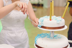 Bride and Wedding Cake. Bride taking slice of wedding cake Stock Photo