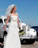 The bride and the wedding car. Bride on the background of the wedding car Royalty Free Stock Photos