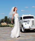 The bride and the wedding car. Bride on the background of the wedding car Royalty Free Stock Photography