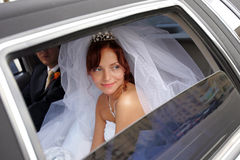 Bride in Wedding Car. A portrait of a beautiful bride in a wedding car limousine. She is looking out of an open window Stock Images