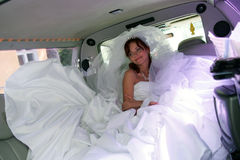 Bride in Wedding Car. A portrait of a beautiful bride in a wedding car limousine. She is sat on the back seat smiling Royalty Free Stock Images