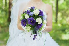 Bride after the wedding ceremony in the sun park holds a beautiful bouquet. The bride after the wedding ceremony in the sun park holds a beautiful bouquet of Royalty Free Stock Photo