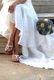 Bride-Wedding Dress. Lower half body portrait of bride in long white wedding dress with bouquet outdoors Royalty Free Stock Photo