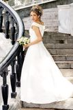 Bride in Wedding Dress. A portrait of a bride in a traditional white wedding dress. She is stood on some strps holding a bouquet of flowers Stock Image