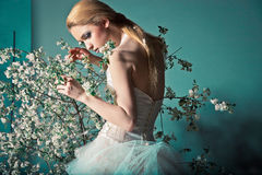 Bride in wedding dress behind bush with flowers Stock Photo