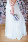 The bride in a wedding dress with a bouquet of flowers. Bride in wedding dress holding a bouquet of flowers on stone wall background stock photos