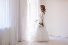 Bride in wedding dress with a bouquet of flowers. In a white room stock photos