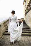 Bride in wedding dress on castle stairs in cloudy day Stock Photos
