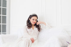 The bride in a wedding dress with a Crown sitting on a white sofa Stock Images
