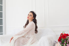The bride in a wedding dress with a Crown sitting on a white sofa Royalty Free Stock Photos