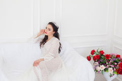 The bride in a wedding dress with a Crown sitting on a white sofa Royalty Free Stock Images