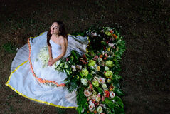 Bride in wedding dress flower looks up and smiles Stock Photo