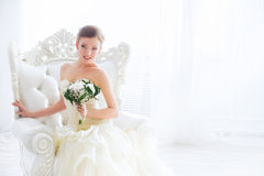 Bride in wedding dress with flowers and staircase. The bride sits on a antique chair with a bouquet in a wedding dress indoor Royalty Free Stock Photos
