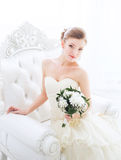 Bride in wedding dress with flowers and staircase. The bride sits on a antique chair with a bouquet in a wedding dress indoor Stock Image