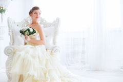 Bride in wedding dress with flowers and staircase. The bride sits on a antique chair with a bouquet in a wedding dress indoor Stock Photography
