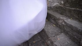 The bride in a wedding dress going up the stairs