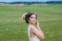 Bride in wedding dress on the green field of the golf club Stock Photography