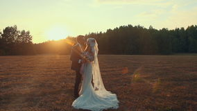 Bride in wedding dress holding bouquet in field with in rays of setting sun. Loving and happiness newlyweds in a field at sunset summer day, embrace and kiss stock video