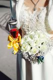 A bride in a wedding dress is holding a bouquet of white roses and a glass of wine. stock photo
