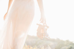 Bride in wedding dress holding a shoes at sunset. Stock Photos