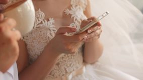 Bride in wedding dress holding smartphone in hands. Groom is drinking cappuccino.