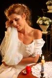 Bride in wedding dress holding veil. Girl undresses for night. Stock Photo