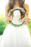 Bride in wedding dress holding a wreath of lights Stock Photo