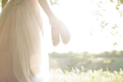 Bride in wedding dress holds shoes against sun. fine art photography Stock Photography
