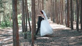 Bride in a wedding dress jumps into the hands of the groom, the action takes place in the forest, slow motion. Bride in wedding dress jumps into the hands of stock footage