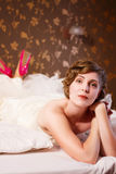 Bride in a wedding dress lies on bed Stock Photography