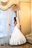 Bride in wedding dress looks out the window Stock Image