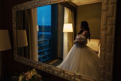 Bride in wedding dress. At luxurious suites, a luxury apartment. A lush, lacy long dress. Light and huge veil. The bride clings to the handrail and looks into stock images