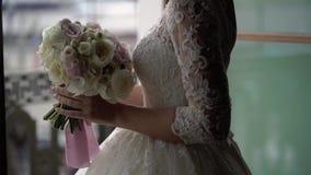 Bride in wedding dress near balcony. With bouquet stock footage