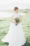 Bride in wedding dress posing on grass with beautiful landscape background Royalty Free Stock Image