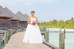Bride in wedding dress posing near the water villas Royalty Free Stock Images